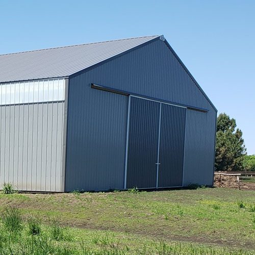 post frame building with gray metal siding