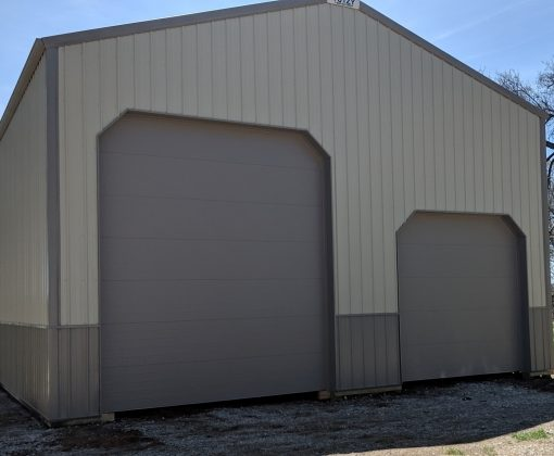 tan and brown post frame building with two garage doors